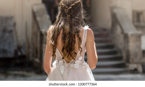Brunette woman in wedding backless dress posing in city