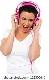 Brunette women enjoying rocking with loud music isolated over white