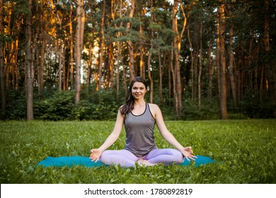 a brunette women in a sports uniform performs the Siddhasana asana in nature at sunset