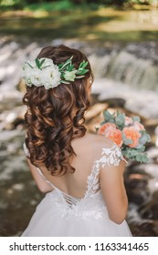 Brunette young bride with long beautiful curly hair. Woman with bridal elegant hairstyle decorated with fresh white flowers. Vertical color photography.