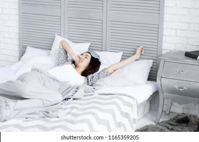 Brunette young cute girl female woman lying in bed with sleeping mask and yawning in light interior room. Morning wake up concept