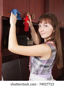 Brunette young girl cleans a furniture indoor