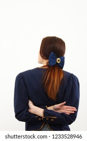 Brunette young lady stand in front of white wall in blue waistcoat with big blue bow on her hair
