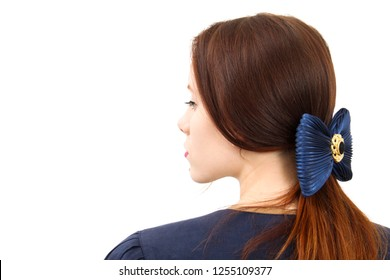Brunette young lady stand in front of white wall in blue waistcoat with big blue bow on her hair with cold face expression