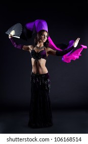 Brunette young woman dancing oriental dance