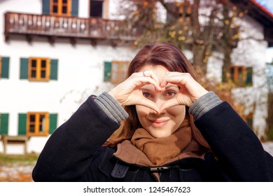 brunette young woman forming heart with hands in front of bavarian house