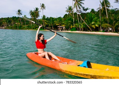 Brunette young woman girl in red bikini paddling on red, orange, yellow kayak in the blue water. Asia. Thailand
