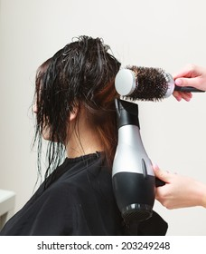 Brunette young woman girl with wet hair in hairdressing beauty salon. Hairstylist hairdresser with dryer and brush drying hair of female client.