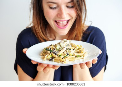 brunette young woman holding a white plate with pasta and cheese