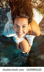 brunette young woman sitting on a cliff, looking up into the camera, with water underneath her