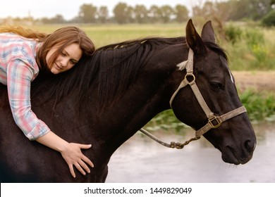 brunette young woman sitting on her black horse