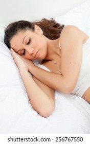 Brunette young woman sleeping in her bed
