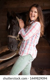 brunette young woman standing with her black horse and laughs