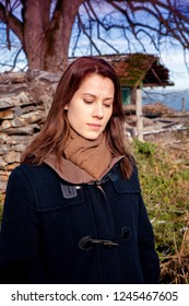 brunette young woman standing outdoors and looking sad