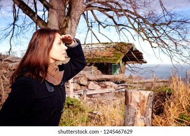 brunette young woman standing outdoors and enjoying the view