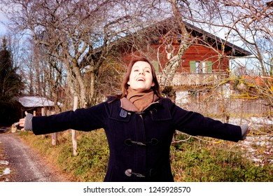 brunette young woman standing outdoors in autumn and spreading her arms