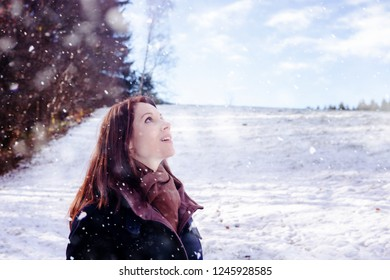 brunette young woman standing outdoors and enjoying the snow
