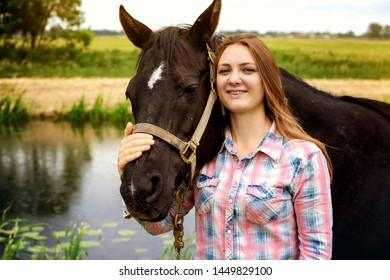 brunette young woman standing outdoors with her black horse