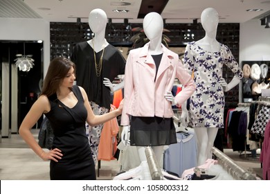 Brunette, young woman in a store or boutique shopping for clothing.