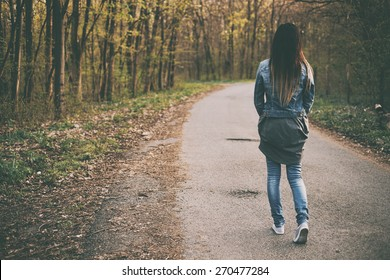 Brunette young woman walking the forest road