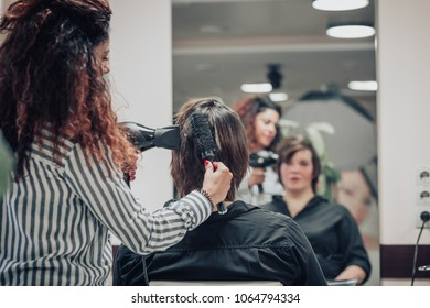 Brunette young woman at work at the hairdresser salon. Hairdresser making hairstyle.