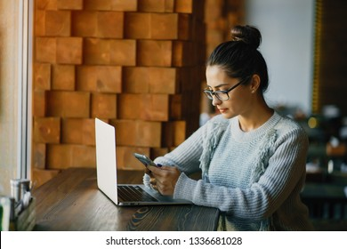 brunetter woman working on her laptop at a restaurant