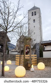 Brunico, Italy, 14 December 2014: christmas decorations in the San Candido village in Alpa Pusteria region. In the background the white tower of San Candido