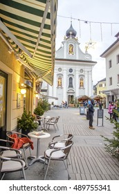 Brunico, Italy, 14 December 2014: A bistro chairs with the church of San Candido in the background during winter holidays