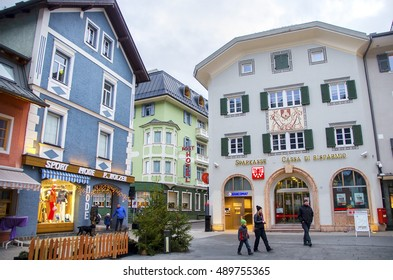 Brunico, Italy, 14 December 2014: family walk through the coloful buildings and shops in the center of the San Candido village during the christmas holidays