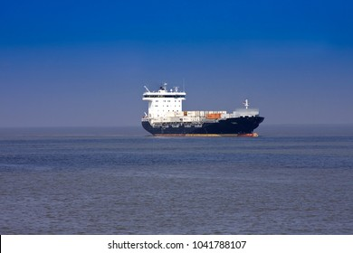 BRUNSBUETTEL,GERMANY, -APRIL 19, 2018:Container-operated ship drives at Brunsbüttel on the Elbe to Hamburg, Lower Saxony, Germany