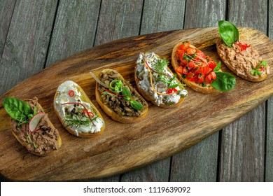 Bruschetta and antipasti crostini set made of baguette tomato, meat pate, olives, cream cheese and tuna salad. Classic Italian food. Top view.