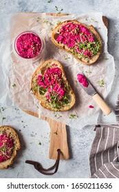 Bruschetta mit Beet hummus dekoriert mit geschnittenen Nüssen und Mikrogrün. Veganische Rezepte, pflanzliche Gerichte. Grünes Wohnkonzept. Bio-Lebensmittel. Vegetarische Küche. Brot mit rosafarbener Tauchsoße