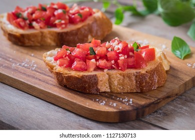 Bruschetta bread with chopped tomato and basil on wooden plate