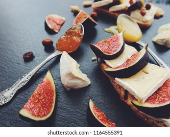 Bruschetta with cheese, fresh figs, nuts and honey. Sandwiches with cheese, figs and assorted nuts on a black stone board. Top view. Side view.