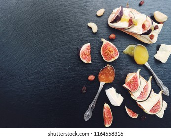 Bruschetta with cheese, fresh figs, nuts and honey. Sandwiches with cheese, figs and assorted nuts on a black stone board. Overhead. Copy space.