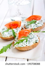 Bruschetta with cheese and rocket spread and slice of tomato