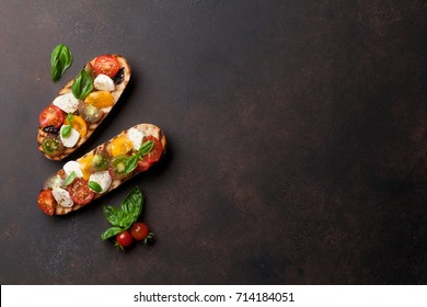 Bruschetta with cherry tomatoes, mozzarella and basil. Caprese salad. Top view with copy space