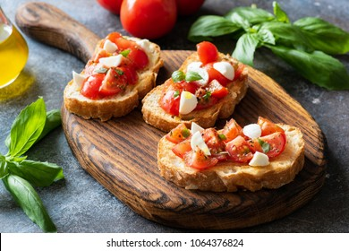 Bruschetta with cherry tomatoes and mozzarella cheese on wooden cutting board. Italian cuisine. Antipasti or appetizer