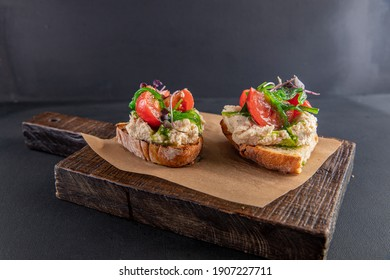 Bruschetta with chicken pate with tomatoes and basil.on a craft board  - Shutterstock ID 1907227711