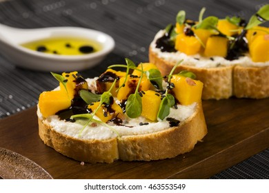 Bruschetta with chopped mango, cress, basil and goat cheese on fresh baguette on the table.