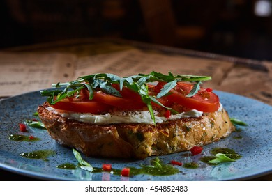 Bruschetta with cottage cheese, tomatoes and arugula served on blue plate.
