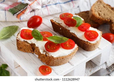 Bruschetta with cream cheese, cherry tomatoes and basil on a wooden table