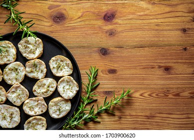 Bruschetta crostini with fresh spreadable cheese and oregano arranged on a black plate on a rustic wooden table adorned with fresh sprigs of rosemary