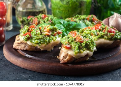 Bruschetta with fresh pesto, mozzarella and cherry tomatoes on cutting board
