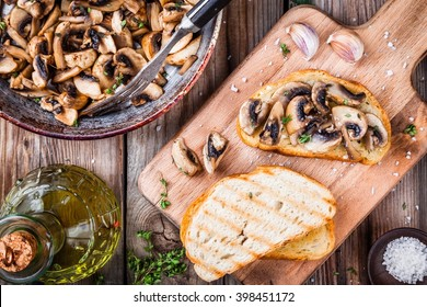 Bruschetta with fried mushrooms on wooden cutting board