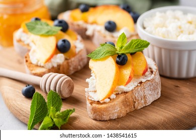 Bruschetta with fruits and soft cheese on wooden cutting board. Closeup view. Toasted baguette bread with soft cheese, peach, honey and blueberries