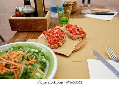 Bruschetta and a garden salad setting on a table.