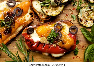 Bruschetta with grilled bell pepper, zucchini, olives and mozzarella cheese. Vegetarian dish
