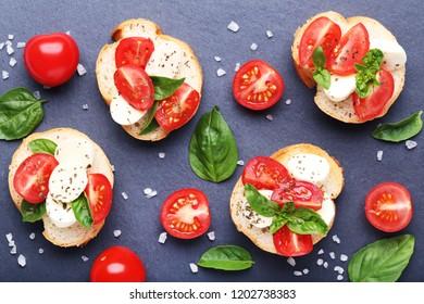 Bruschetta with mozzarella, tomatoes and basil leafs