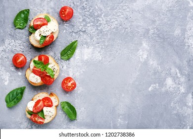 Bruschetta with mozzarella, tomatoes and basil leafs on grey wooden table